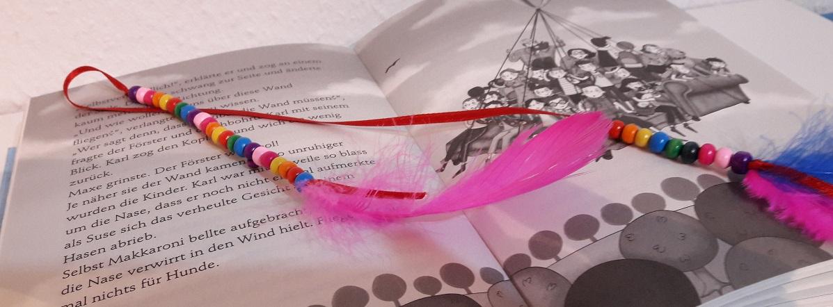 Hübsche Lesezeichen aus bunten Perlen und Federn – auch für den Kindergeburtstag
